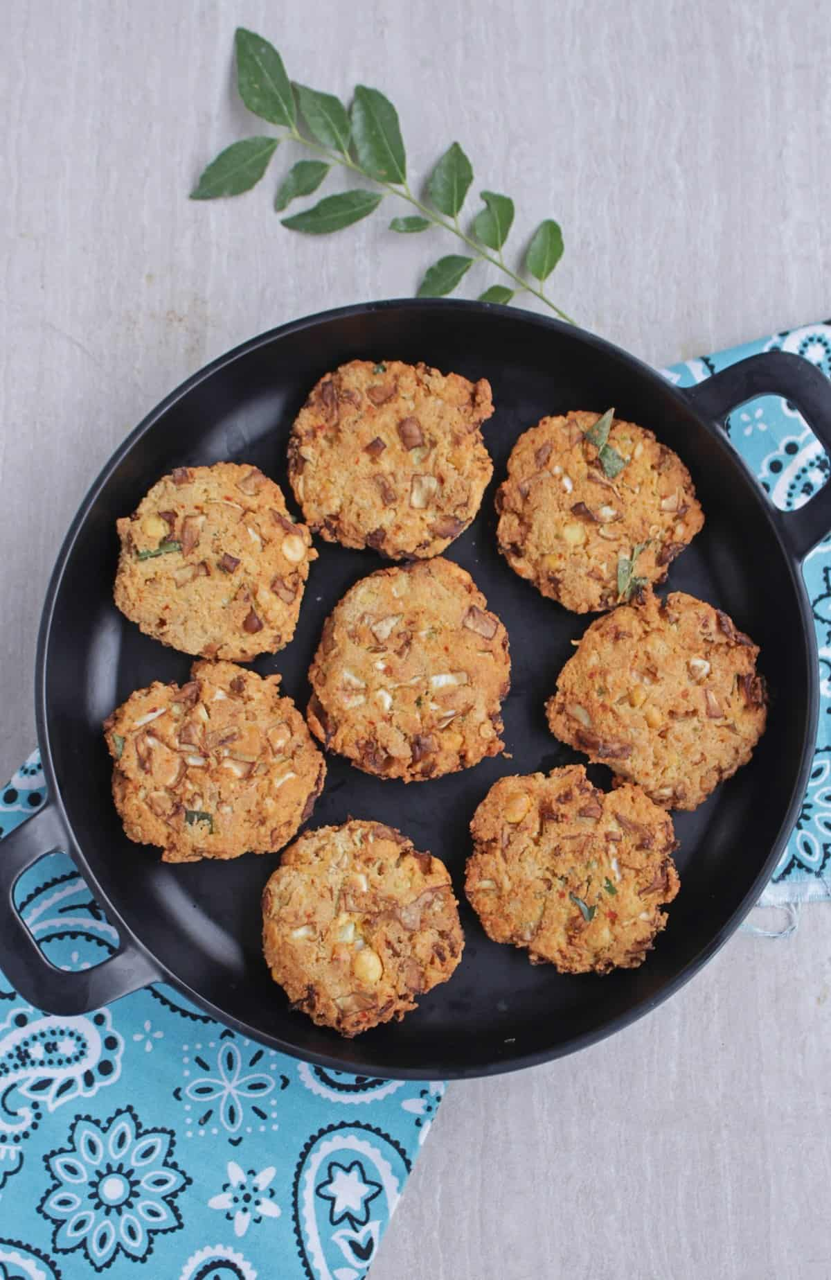 Cabbage vadai in a black plate with curry leaf in the background
