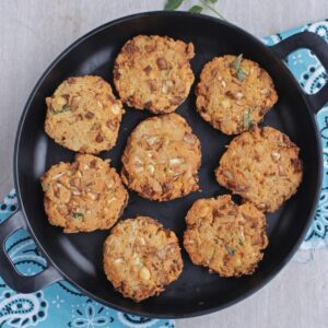 8 fritters arranged in a black round plate