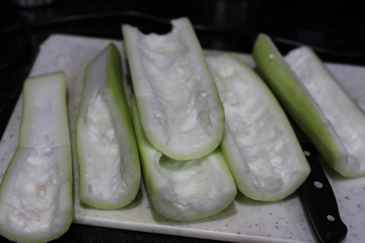Peeled and chopped bottle gourd on a cutting board