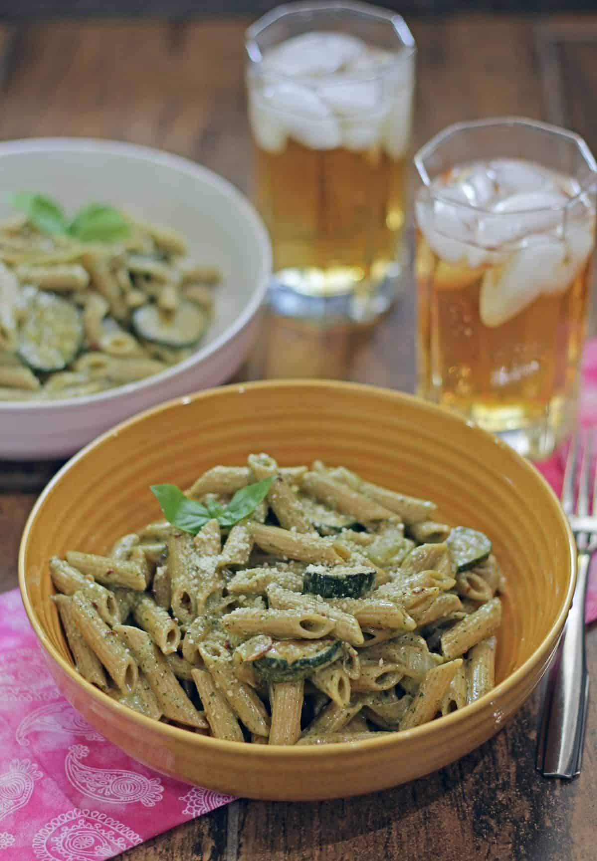 Pasta with zucchini in a yellow bowl with a drink in the background.