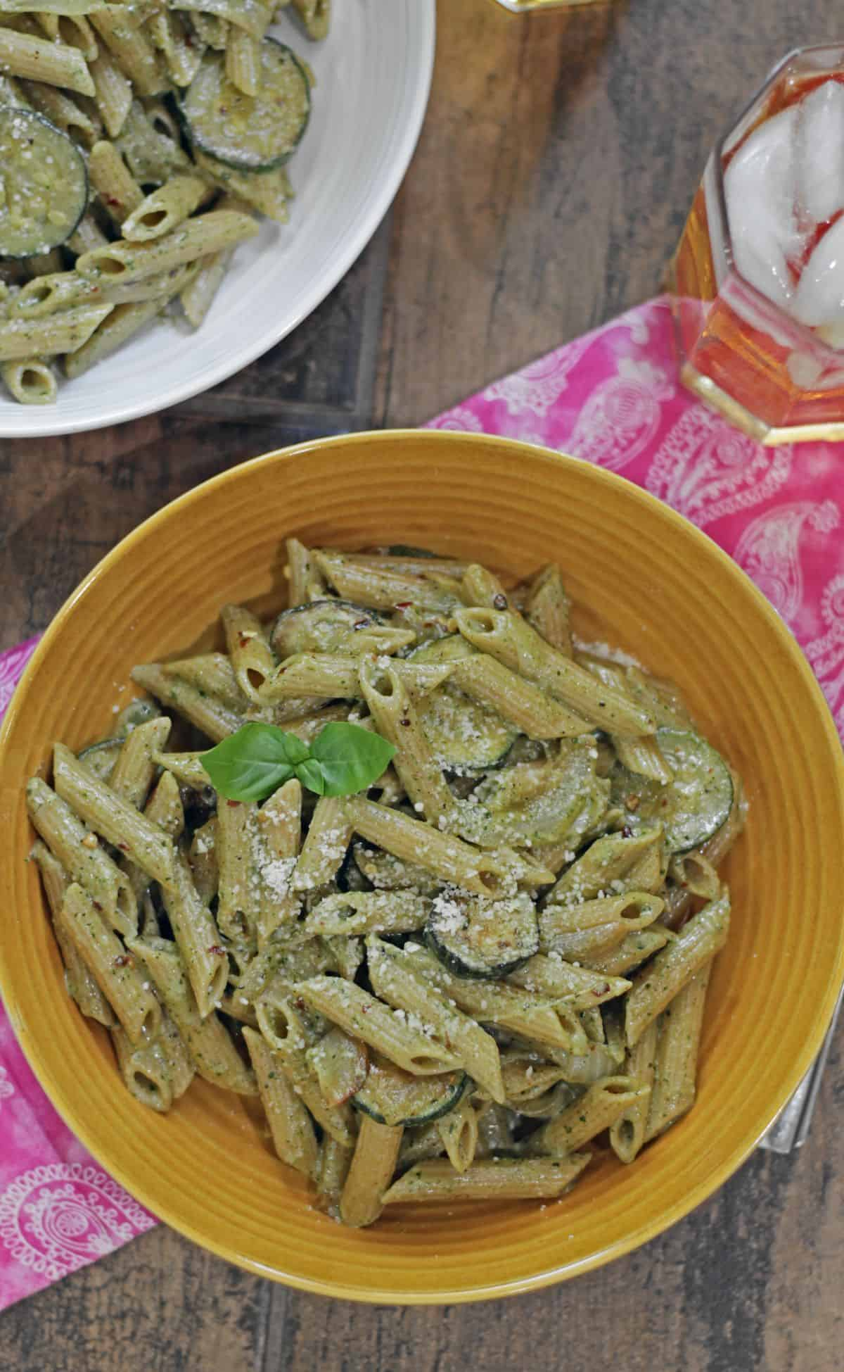 zucchini pesto pasta in a yellow bowl garnished with fresh basil