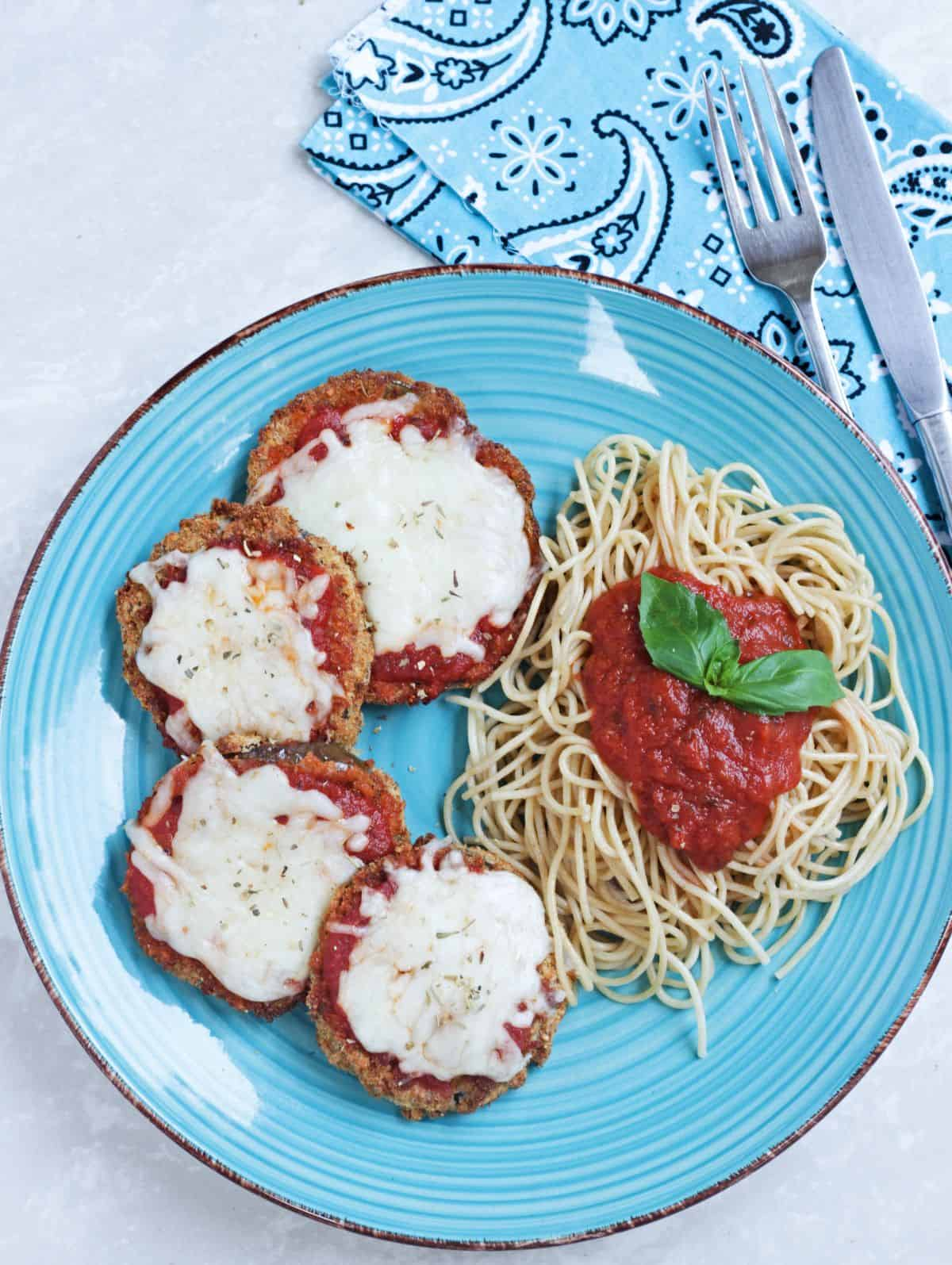 Eggplant parmesan with pasta and sauce in a blue plate