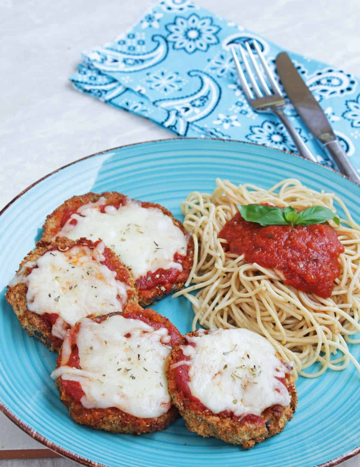 Eggplant parmesan with melted cheese and spaghetti on a plate
